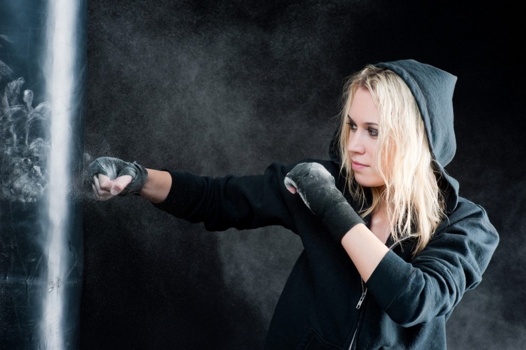 Blond boxing woman in black punching bag