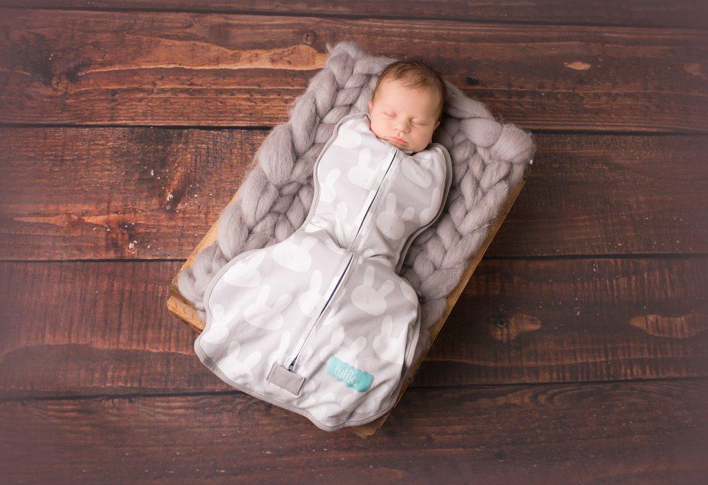 Dziecko śpiące w otulaczu antykolkowym Tulik